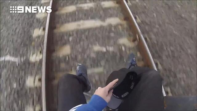 Train surfer films dangerous stunt on moving carriage
