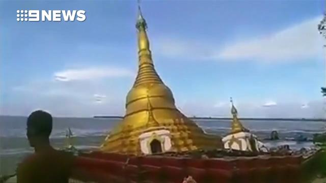 Onlookers helpless to stop golden temple sliding into river