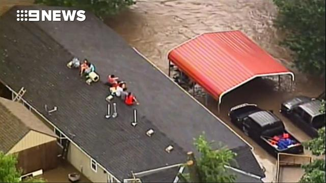 Family stranded on roof for eight hours as US floods turn deadly